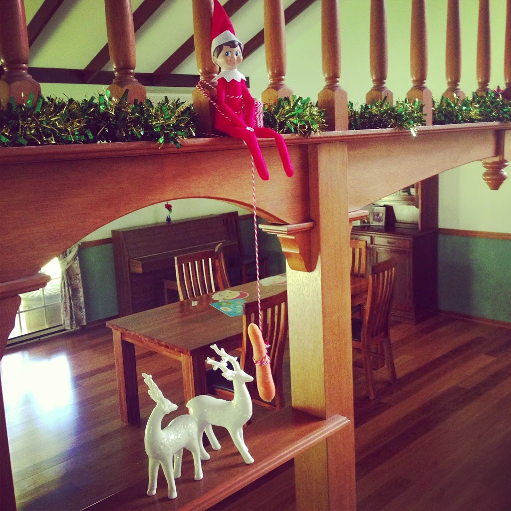 Elf on the shelf feeding a reindeer.
